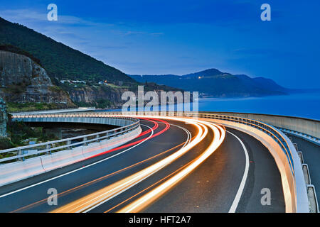 Sea Cliff Bridge iconic highway on Grand Pacific drive from Sydney to Wollongong in Australia pacific coast at sunset. - Stock Photo