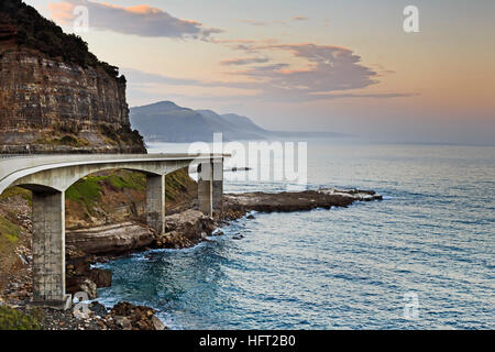 Side view of Sea Cliff Bridge on Grand Pacific Drive in Australia. Bright sunset over pacific ocean from scenic - Stock Photo