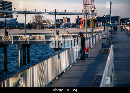 A fisherman on a pier in Coney Island New York on a bright winter day - Stock Photo
