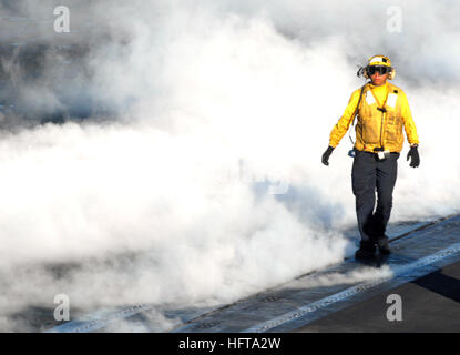 061116-N-2959L-394 Pacific Ocean (Nov. 16, 2006) - An aviation boatswain's mate (handling) walks back onto catapult - Stock Photo