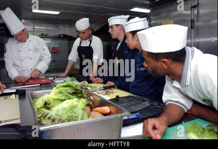 070715-N-9150R-055  PACIFIC OCEAN (July 14, 2007) - Culinary specialists watch as Executive Chef James Koskiniemi - Stock Photo