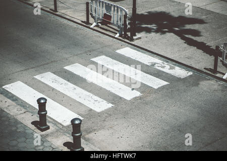 Pedestrian crossing, zebra traffic cross way over narrow road with two small metal columns in front on sunny day - Stock Photo