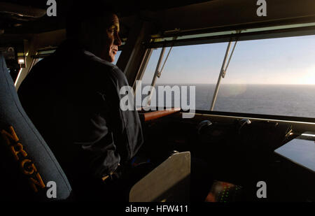 USS Ronald Reagan (CVN 76) executive officer, Capt. Kevin Couch, watches over flight operations from the bridge - Stock Photo