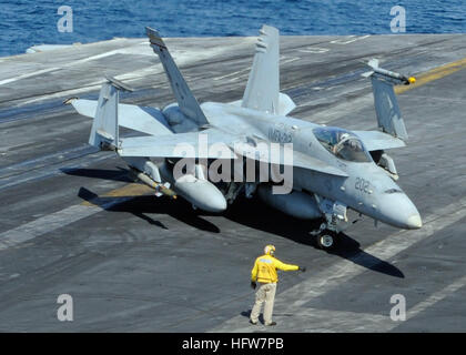 A plane director guides the pilot of an F/A-18C Hornet as it taxis across the flight deck aboard the aircraft carrier - Stock Photo