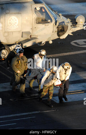 Medical personnel aboard the aircraft carrier USS Ronald Reagan (CVN 76) help unload a patient from an HH-60H Seahawk - Stock Photo