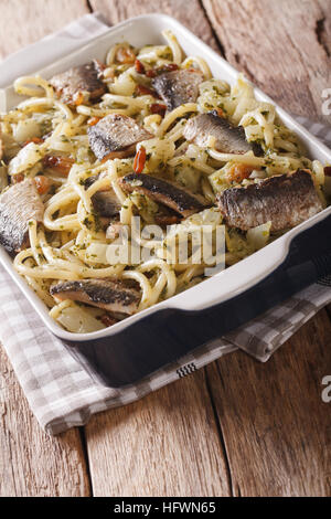Italian food: pasta with sardines, fennel, raisins and pine nuts close up in baking dish on the table. vertical - Stock Photo