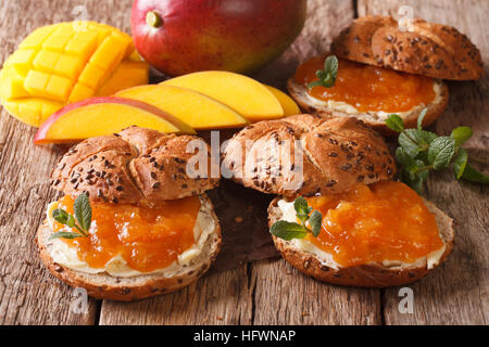 Sweet freshly baked rolls with mango jam, butter and mint close-up on the table. horizontal - Stock Photo