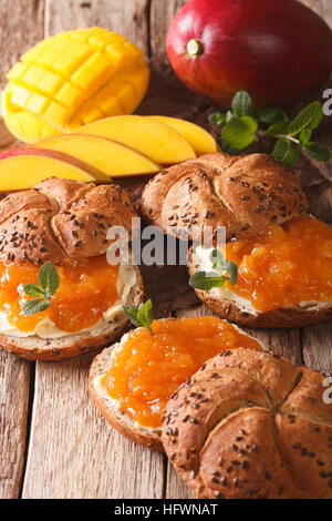 Sweet buns with mango marmalade, butter and mint close-up on the table. vertical - Stock Photo