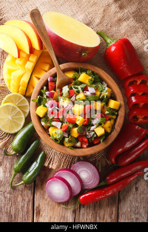 Salsa with mango, cilantro, onions and peppers close up in a bowl and ingredients on the table. vertical view from - Stock Photo