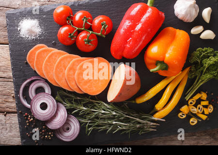 Vegetable Ingredients: sweet potatoes, peppers, tomatoes, onions, garlic, rosemary and spices close-up on a slate - Stock Photo
