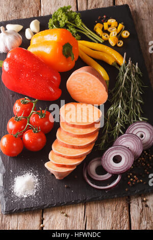 Preparing ingredients: raw sweet potatoes, peppers, tomatoes, onions, garlic, rosemary and spices close-up on the - Stock Photo