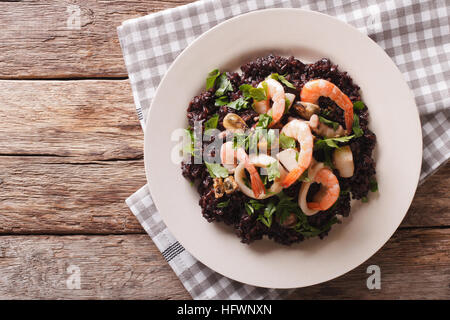 Paella from black rice with seafood close-up on a plate on the table. horizontal view from above - Stock Photo