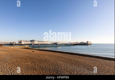 The Victorian Brighton Palace Pier and shingle Brighton beach deserted on a sunny winter day in November with blue - Stock Photo