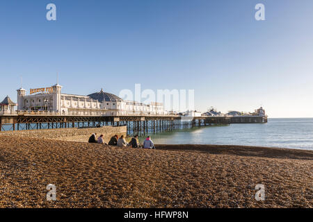 The Victorian Brighton Palace Pier and shingle Brighton beach with a small group on a sunny winter day in November - Stock Photo