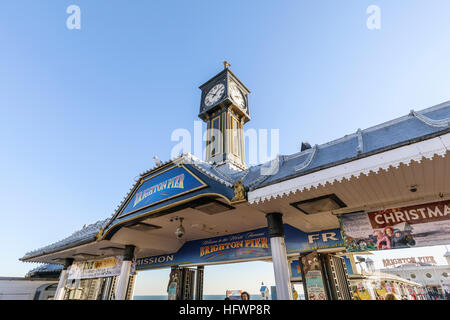 Entrance to the Victorian Brighton Palace Pier on a sunny winter day in November with blue sky - Stock Photo