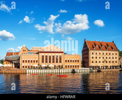 Baltic Philharmonic Hall in old power house, old Royal Granary transformed into the a hotel and red kayaks on Motlawa - Stock Photo