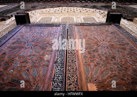 The intricate wooden doors in the Bou Inania madrasa in the medina of Fez, Morocco surrounded by carved plasterwork. - Stock Photo
