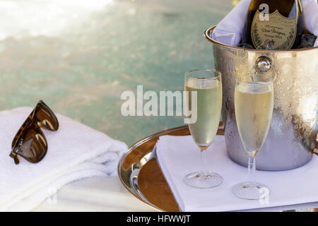 Champagne bottle and flutes with jacuzzi behind - Stock Photo