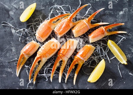 Cooked crab claws with lemon, sea salt and pepper on a concrete background - concept of healthy eating, dieting - Stock Photo