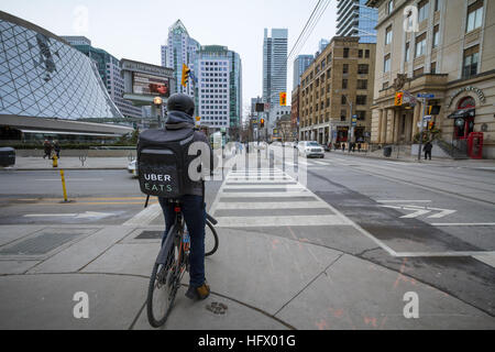 TORONTO, CANADA - DECEMBER 31, 2016: Uber Eats delivery man on a bicycle waiting to cross a street - Stock Photo