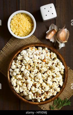 Homemade fresh savory popcorn with cheese, garlic and dried oregano in wooden bowl, photographed overhead with natural - Stock Photo