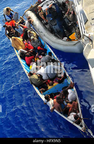 090525-N-4774B-044  GULF OF ADEN (May 24, 2009) Somali migrants in a disabled skiff receive assistance from Sailors - Stock Photo