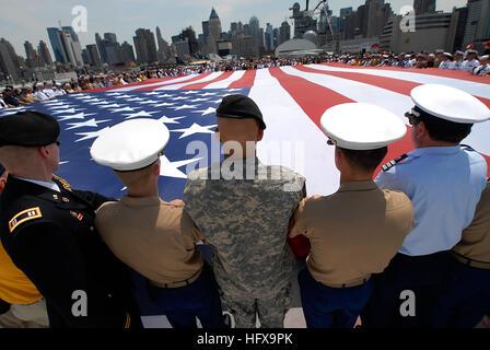 090525-N-5033P-145 NEW YORK (May 25, 2009) Members of the Fleet Week flag detail unfurl a U.S. flag during a Memorial - Stock Photo