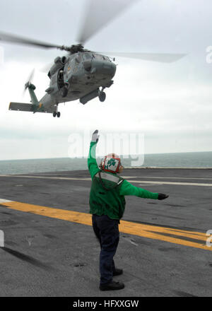 A Sailor aboard the aircraft carrier USS Harry S. Truman  signals the pilot of an HH-60H Sea Hawk helicopter assigned - Stock Photo