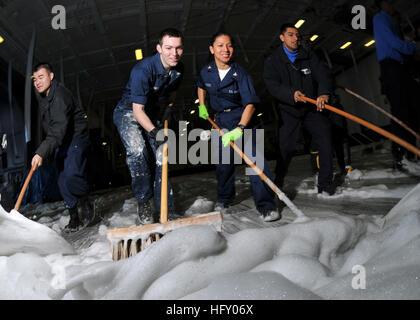 100115-N-1261P-029  PACIFIC OCEAN (Jan. 15, 2010) Sailors scrub the hangar bay for an aqueous film forming foam - Stock Photo