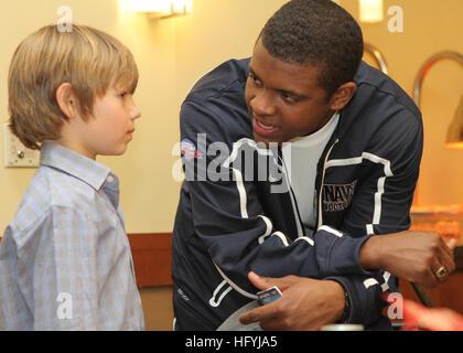 101221-N-3879H-004 SAN DIEGO (Dec. 21, 2010) U.S. Naval Academy quarterback Ricky Dobbs speaks with a child at a - Stock Photo
