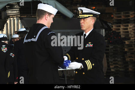 110502-N-OI955-154 PACIFIC OCEAN (May 2, 2011) Cmdr. Stevin Johnson passes the flag to Religious Programs Specialist - Stock Photo