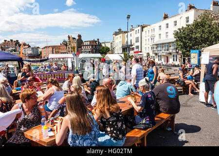English seafront at Ramsgate with people sitting at tables and chairs enjoying drinks during very hot weather in - Stock Photo