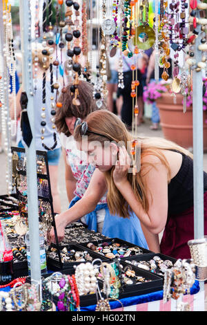 Side view of young long haired blond teenage woman, with her mother, looking at jewellery on outdoor market stall, - Stock Photo