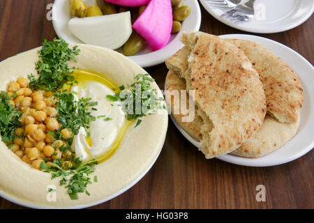 Hummus. A Levantine Arab dip or spread made from cooked, mashed chickpeas, blended with tahini, olive oil, lemon - Stock Photo
