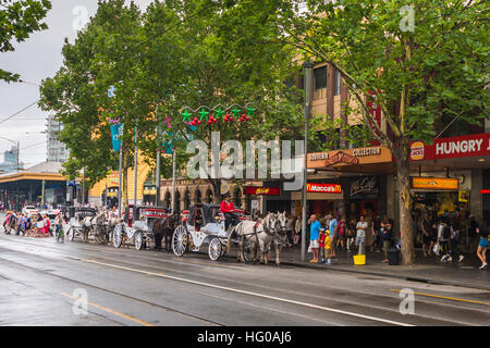 Melbourne, Australia - December 27, 2016: Horse drawn carriages with tourists departing from Flinders Street station - Stock Photo