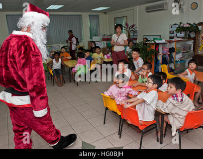 111222-N-DX615-057  SINGAPORE (Dec. 22, 2011) Chief Warrant Officer Marc Lefebvre, dressed as Santa Claus, greets - Stock Photo