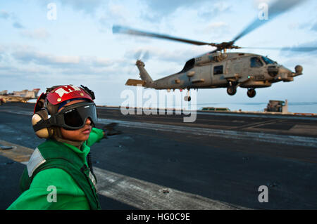120108-N-BT887-007 ARABIAN SEA (Jan. 8, 2012) Airman Joyce Cruz checks for a clear deck before signaling to an MH-60R Seahawk from the Raptors of Helicopter Maritime Strike Squadron (HSM) 71 to take off from the Nimitz-class aircraft carrier USS John C. Stennis (CVN 74). John C. Stennis is deployed to the U.S. 5th Fleet area of responsibility conducting maritime security operations and support missions as part of Operation Enduring Freedom. (U.S. Navy photo by Mass Communication Specialist 3rd Class Benjamin Crossley/Released) US Navy 120108-N-BT887-007 Airman Joyce Cruz checks for a clear dec Stock Photo