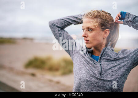 Close up of young female runner tying up hair before a run. Sporty fitness woman on outdoor workout looking away. - Stock Photo