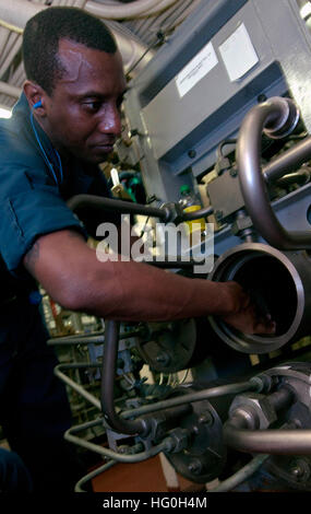Engineman 1st Class Reginald Pierre-Lyss lubricates the lining of water purifier as part of maintenance aboard the - Stock Photo