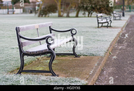 Frost and ice covering a wooden bench in freezing weather in the early morning, in Winter in the UK. - Stock Photo