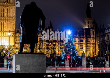 The Houses of Parliament's Christmas tree as seen from behind the Winston Churchill Statue of Parliament Square - Stock Photo