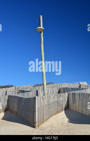 Lamppost and a wooden fence on the beach - Stock Photo