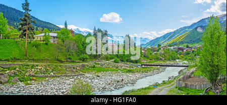 The rocky banks of Mestiachala river with the houses of Mestia and huge mountain ranges on the background, Upper Svaneti, Georgia.