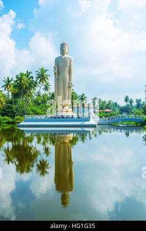 The Tsunami Memorial Buddha Statue reflects in waters of the calm river, Peraliya, Sri Lanka. - Stock Photo