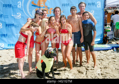 Huntington Beach Junior Lifeguards pose with a sunglasses-wearing Labrador dog in a life jacket. - Stock Photo