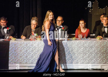 Beauty contest judges eye a formally dressed contestant as she walks by their table in Huntington Beach, CA. - Stock Photo
