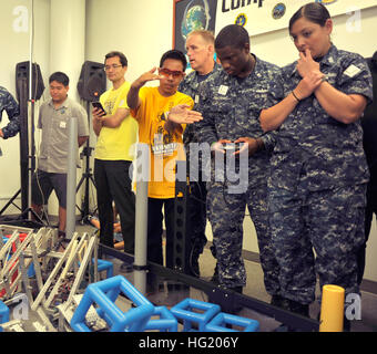 Noah Evile, a sophomore at Mililani High School, instructs Operations Specialist 2nd Class Jerome Williams and Gunner's - Stock Photo