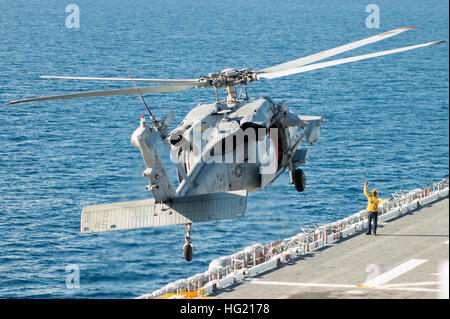 An MH-60S Seahawk with Helicopter Sea Combat Squadron 28 conducts flight operations on board Wasp-class amphibious - Stock Photo