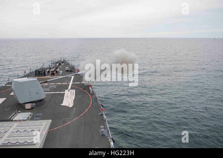 The Arleigh Burke-class guided-missile destroyer USS Winston S. Churchill (DDG 81) fires its Mk 45 5-inch gun during - Stock Photo