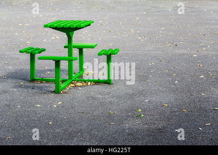 Green metal bench table set in a playground - Stock Photo